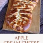 An apple cream cheese braid on a wooden cutting board with a napkin behind it and a green apple with text overlay.