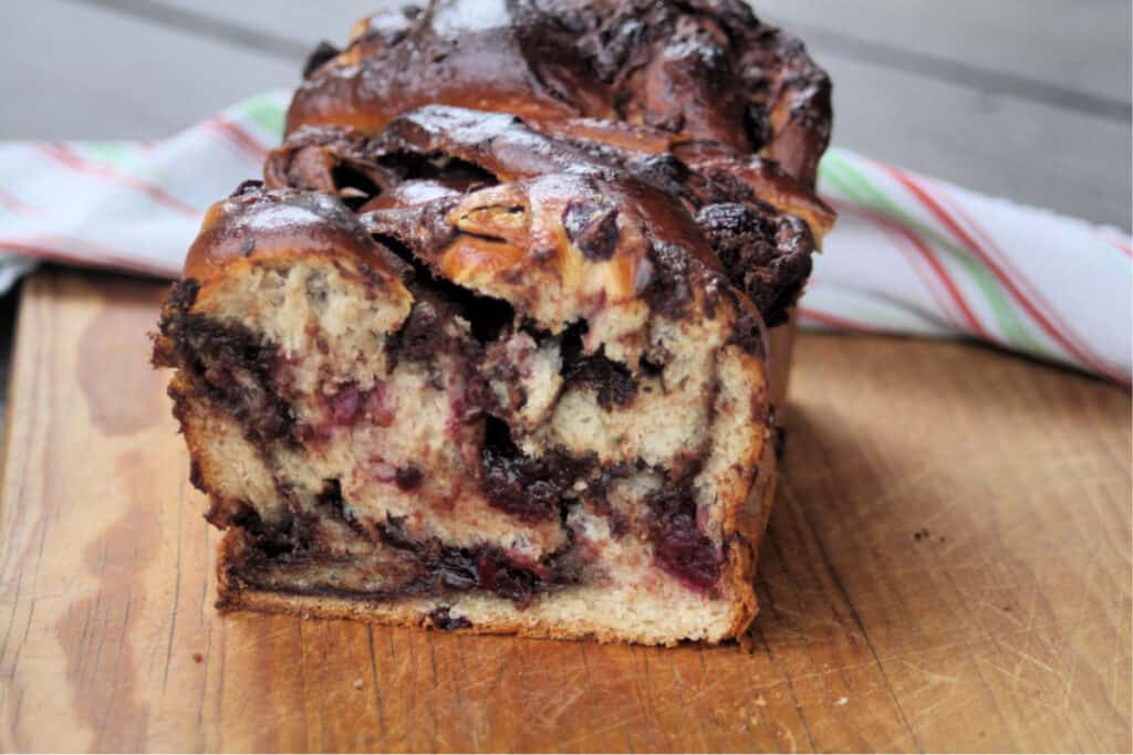 A loaf of chocolate cherry babka with the end cut off exposing the inside sitting on a wooden cutting board.