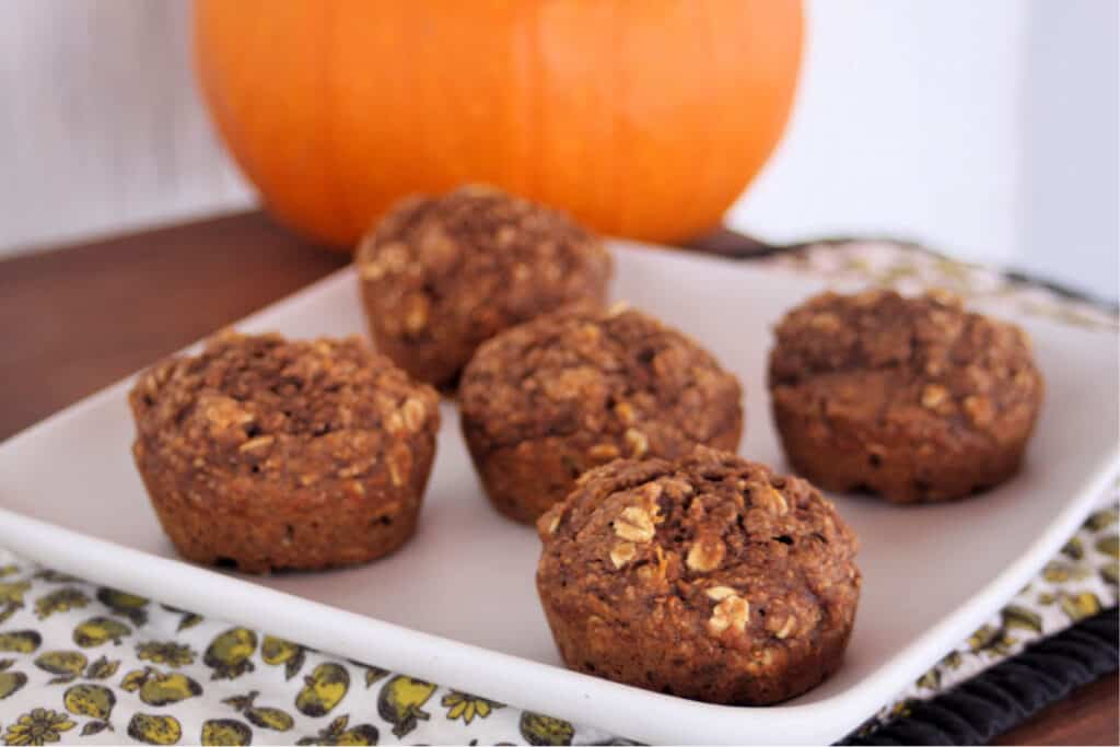 Healthy pumpkin muffins on a square white plate with a pumpkin in the background