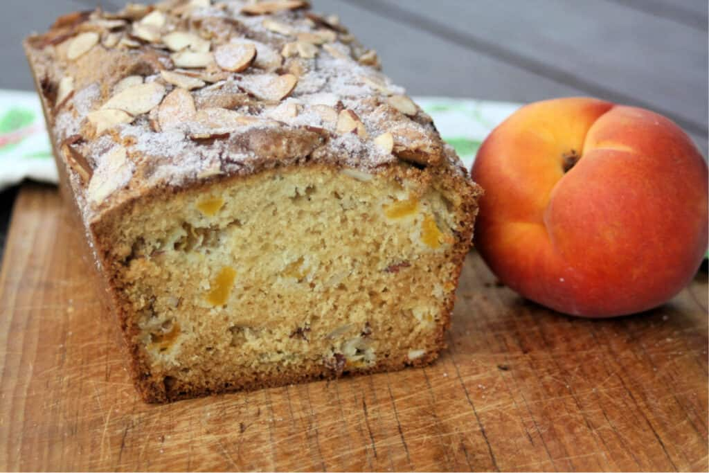 A loaf of peach bread with the end cut off exposing the inside on a cutting board sitting next to a fresh peach.