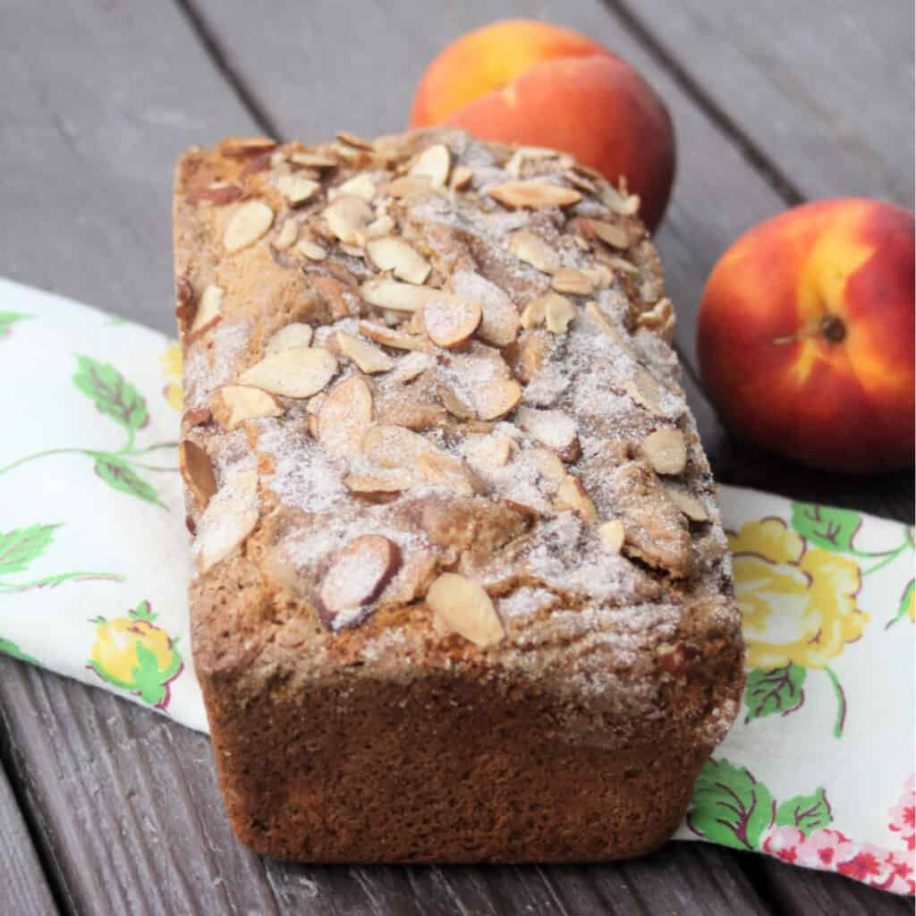 A loaf of peach bread sitting on a floral table runner in front of two fresh peaches.