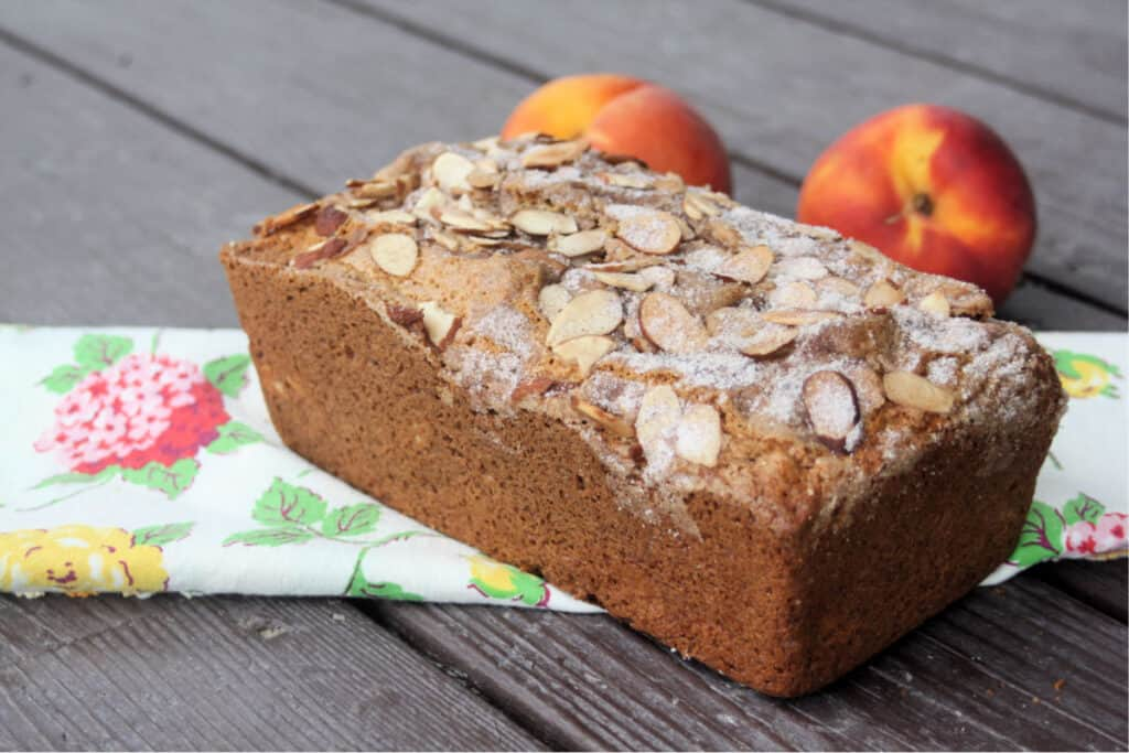 A loaf of peach bread as seen from the side sitting on top of a floral table runner in front of 2 fresh peaches.