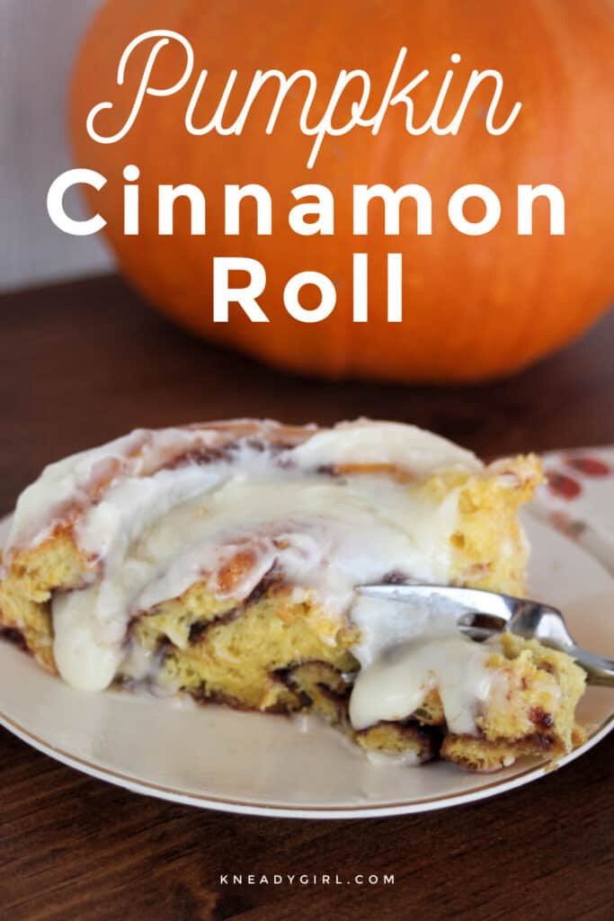 A pumpkin cinnamon roll with cream cheese frosting on a white plat with a fork cutting through the edge, sitting in front of a pumpkin with text overlay.