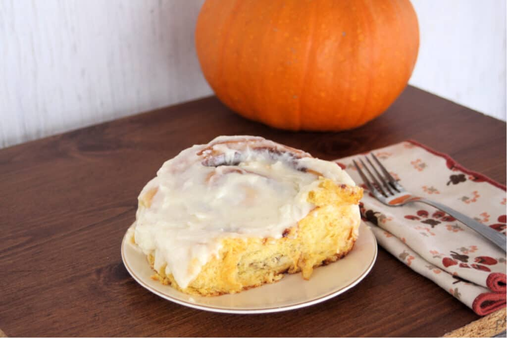 A pumpkin cinnamon roll with cream cheese frosting on a white plate sitting next to a napkin with a fork on top. A whole pumpkin sitting behind.