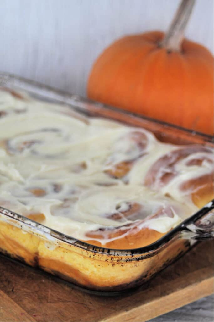 A glass casserole dish full of Pumpkin cinnamon rolls with cream cheese frosting sitting on a wooden cutting board in front of a pumpkin.