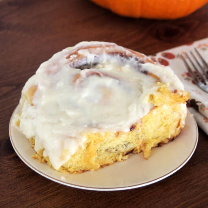 A pumpkin cinnamon roll with cream cheese frosting on a white plate sitting next to a napkin with fork on top.