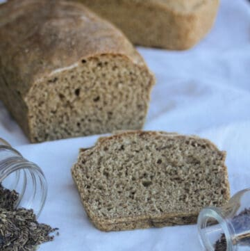 A slice of dill rye bread on a white cloth surrounded by seeds and loaf of bread in the background.