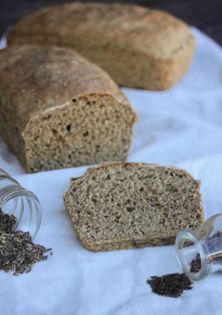 A slice of dill rye bread sitting behind jars of seeds on a white cloth, rest of loaf in the background.