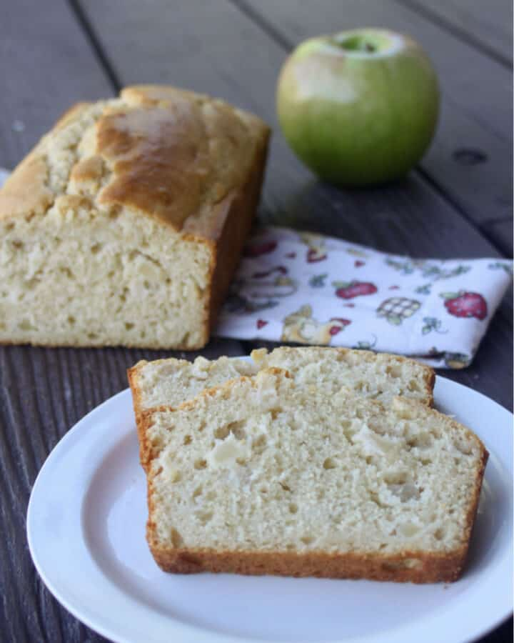 slices of apple bread on a white plate sitting front of the rest of the loaf and a fresh green apple.