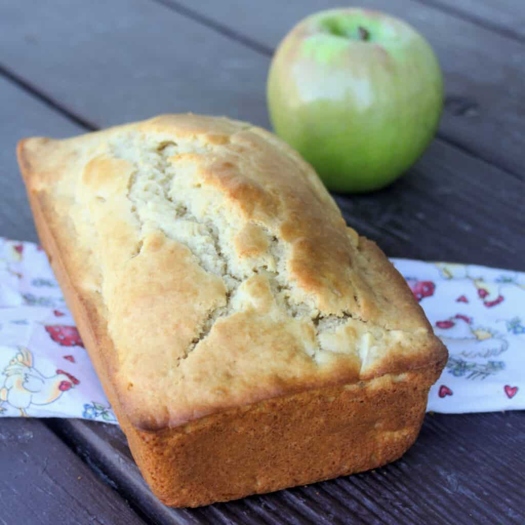 A loaf of apple bread sitting on a linen with green apple in the background.