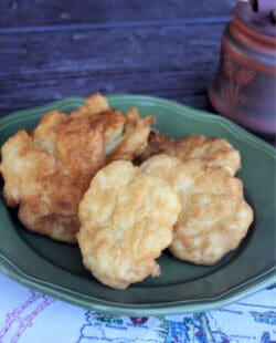 Pieces of fry bread stacked on a green plate sitting on a white linen with a clay honey pot in the background.
