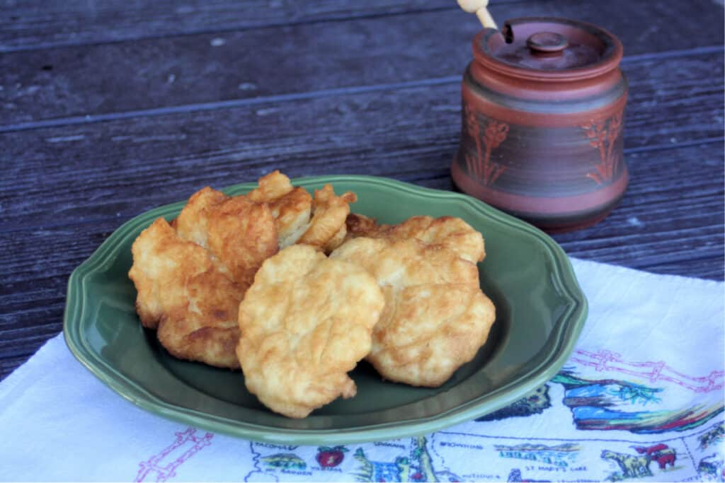 Pieces of fry bread stacked on a green plate sitting on a white linen with a clay honey pot sitting behind them.