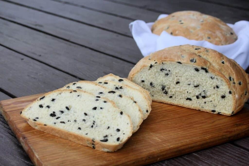 Slices of black olive bread on a board with remaining loaf in background.