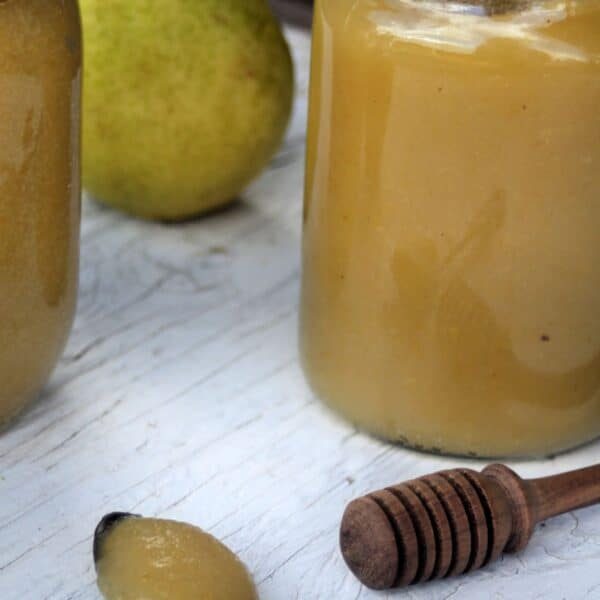 Pear butter on a spoon sitting in front of jars of more pear butter, a honey dipper and fresh pears.