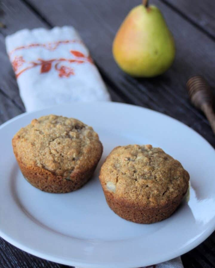 2 muffins on a white plate with a napkin, fresh pear, and honey dipper in the background.