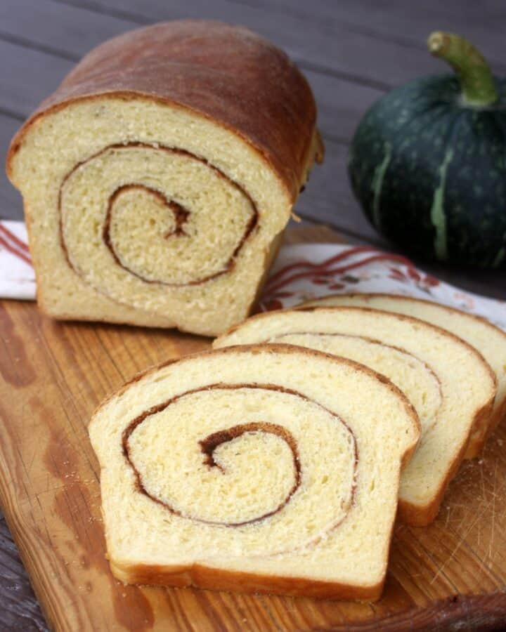 Slices of pumpkin cinnamon swirl bread on a cutting board with remaining loaf behind them and a green pumpkin in the background.