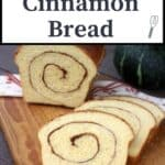 Slices of pumpkin cinnamon swirl bread on a cutting board with remaining loaf behind them and a green pumpkin in the background with text overlay stating: Pumpkin Cinnamon Bread.