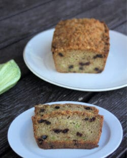 Slices of zucchini raisin bread on a white plate sitting in front of the rest of a loaf on a platter and a bit of fresh zucchini sitting to the left side.