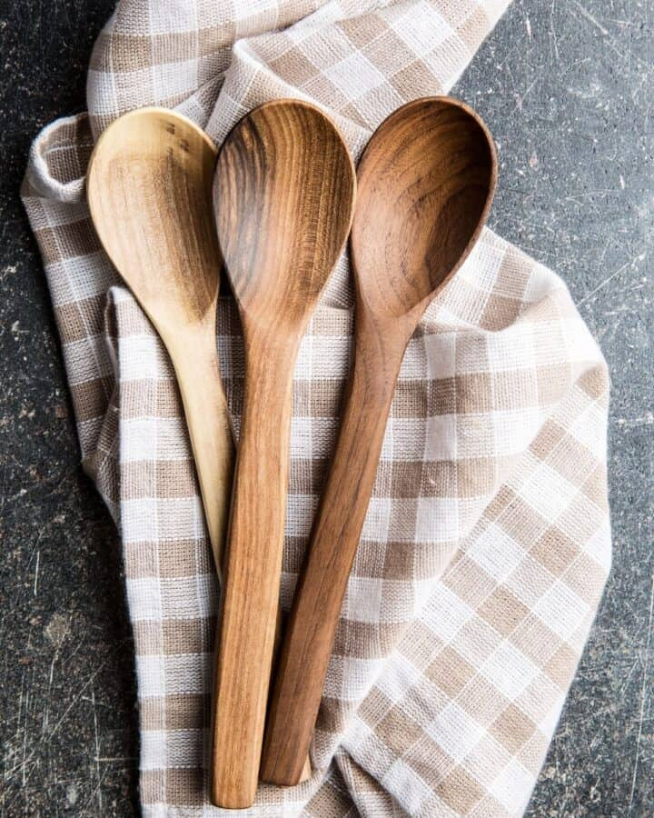 3 wooden spoons sitting on top of a brown and white plaid towel.