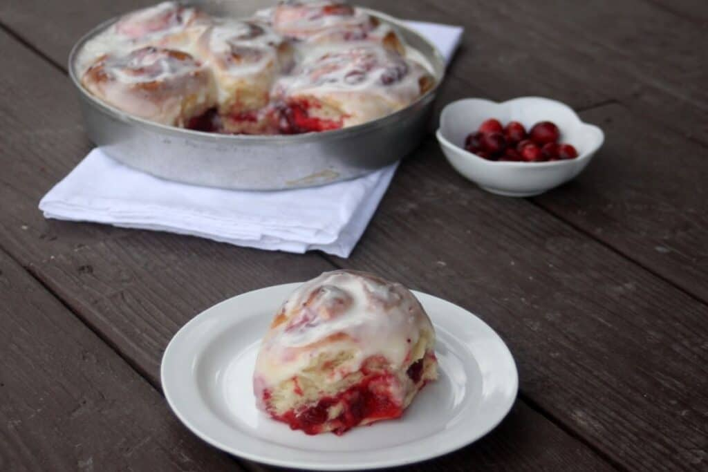 A cranberry sweet roll sitting on a white plate with a napkin sitting underneath a pan full of rolls and a white dish full of fresh cranberries in the background.