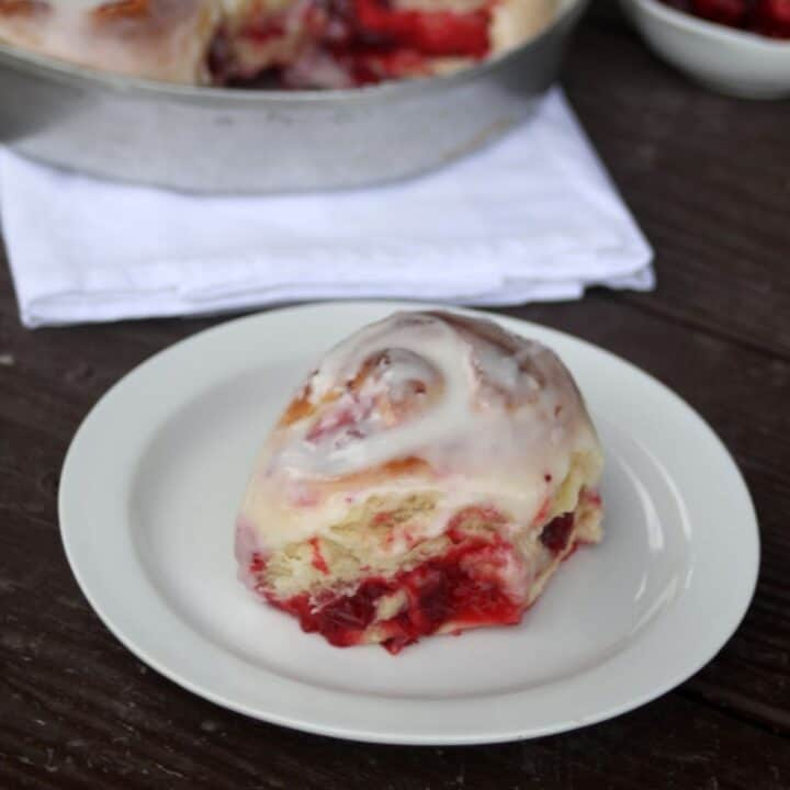 A frosted cranberry sweet roll on a white plate.