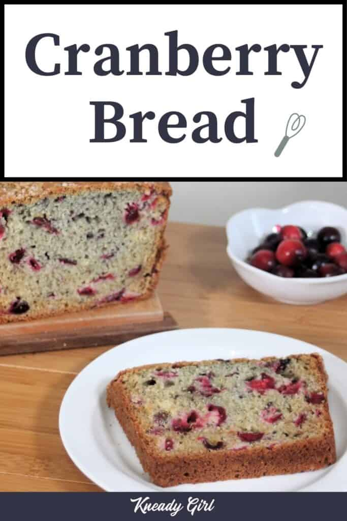 A slice of cranberry bread on a white plate sitting in front of a bowl of cranberries and the remaining loaf with text overlay stating: cranberry bread.