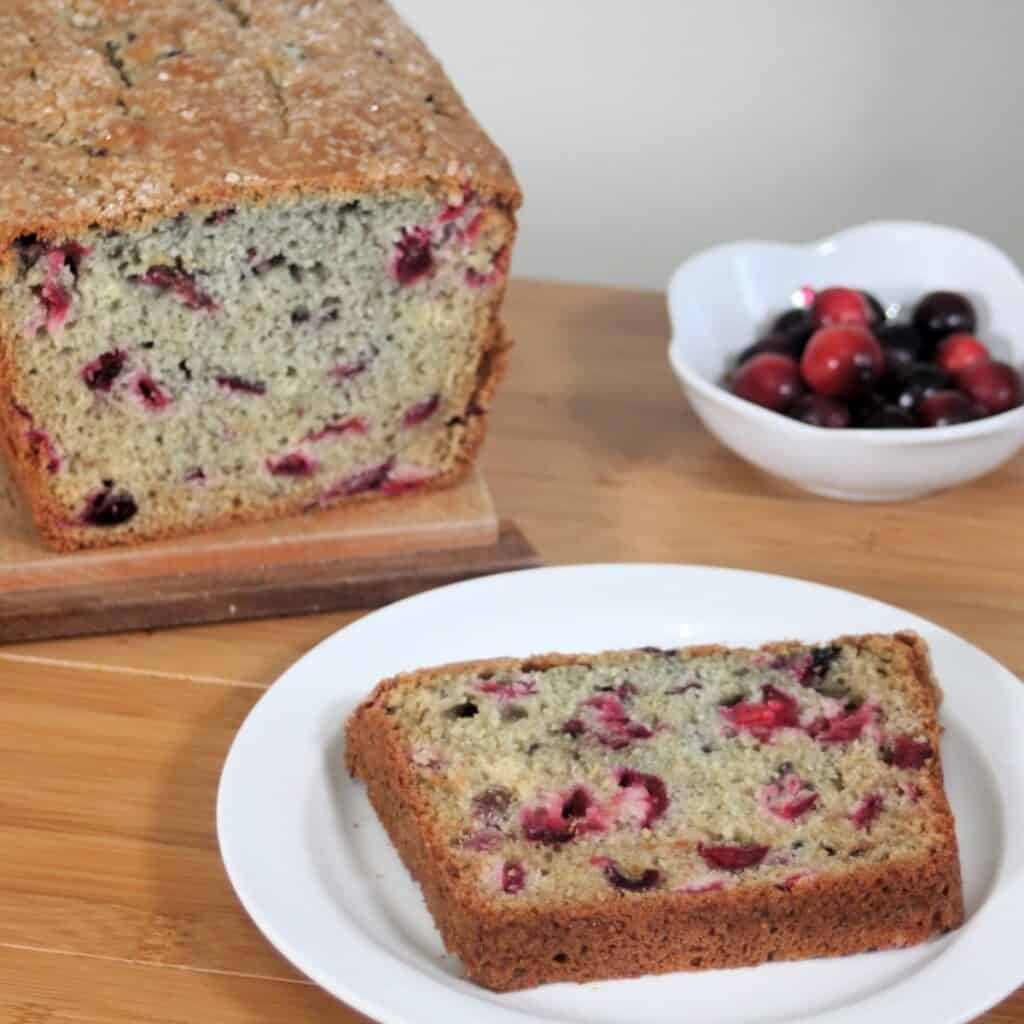 A slice of cranberry bread on a white plate sitting in front of the remaining loaf and a bowl of cranberries.