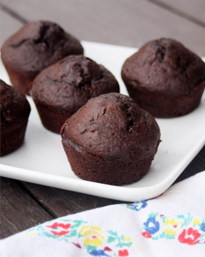 Chocolate muffins on a platter sitting behind a floral napkin.