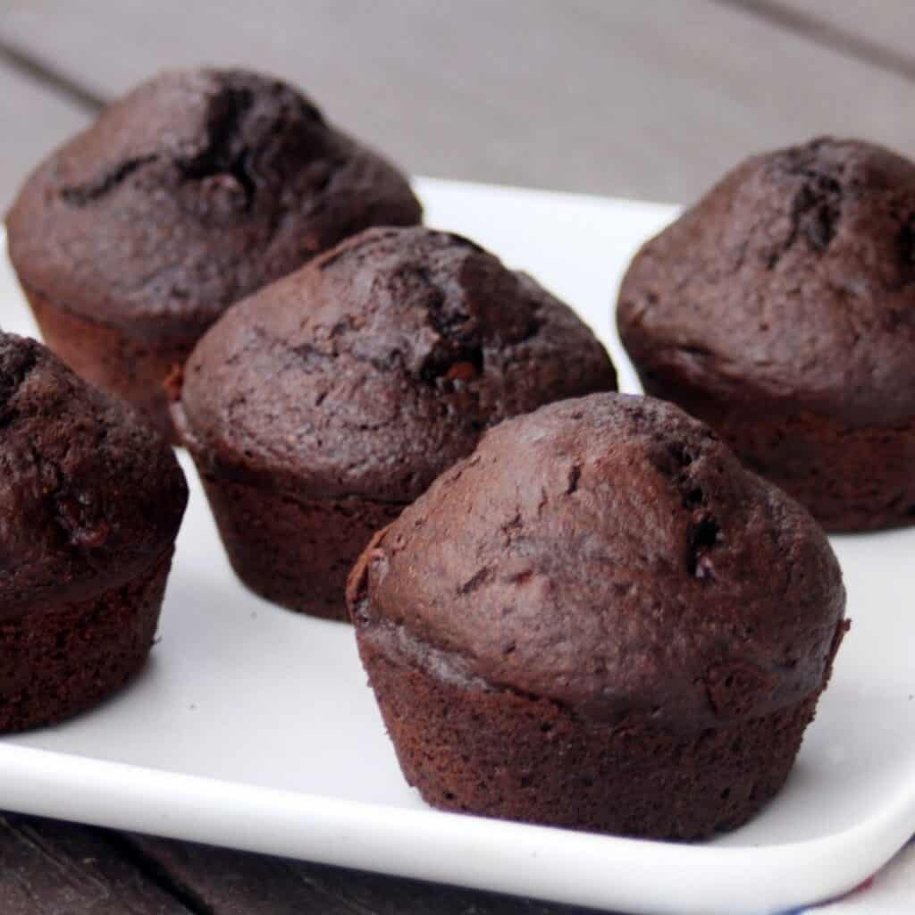 A white plate full of chocolate rye muffins.