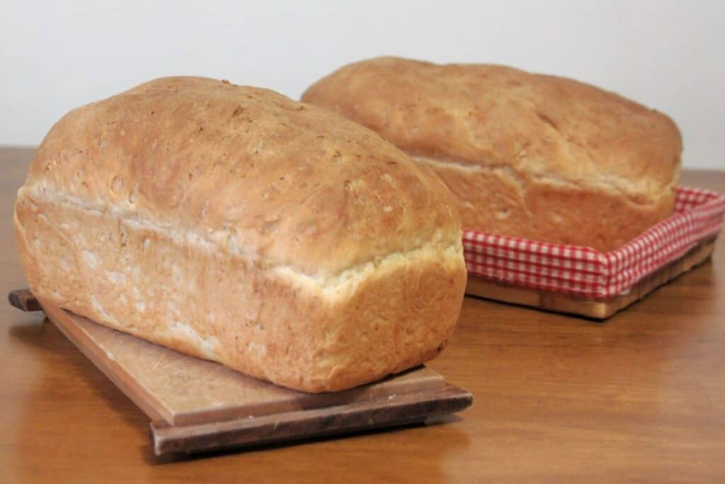 A loaf of cream bread sitting on a cutting board with another sitting behind it in a red and white checked lined basket.