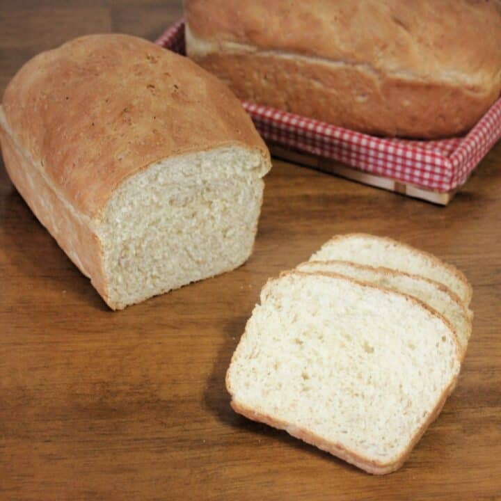 Slices of cream bread on a table sitting in front of the rest of the loaf with another loaf in a basket in the background.