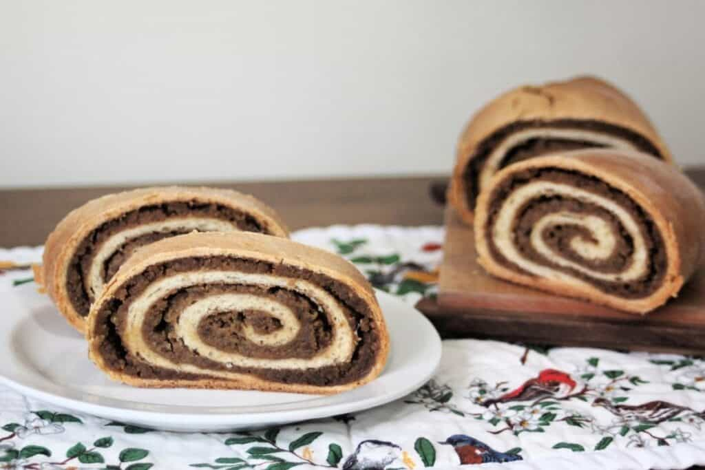 Slices of potica on a white plate sitting on top of a floral table runner with remaining loaf in the background.