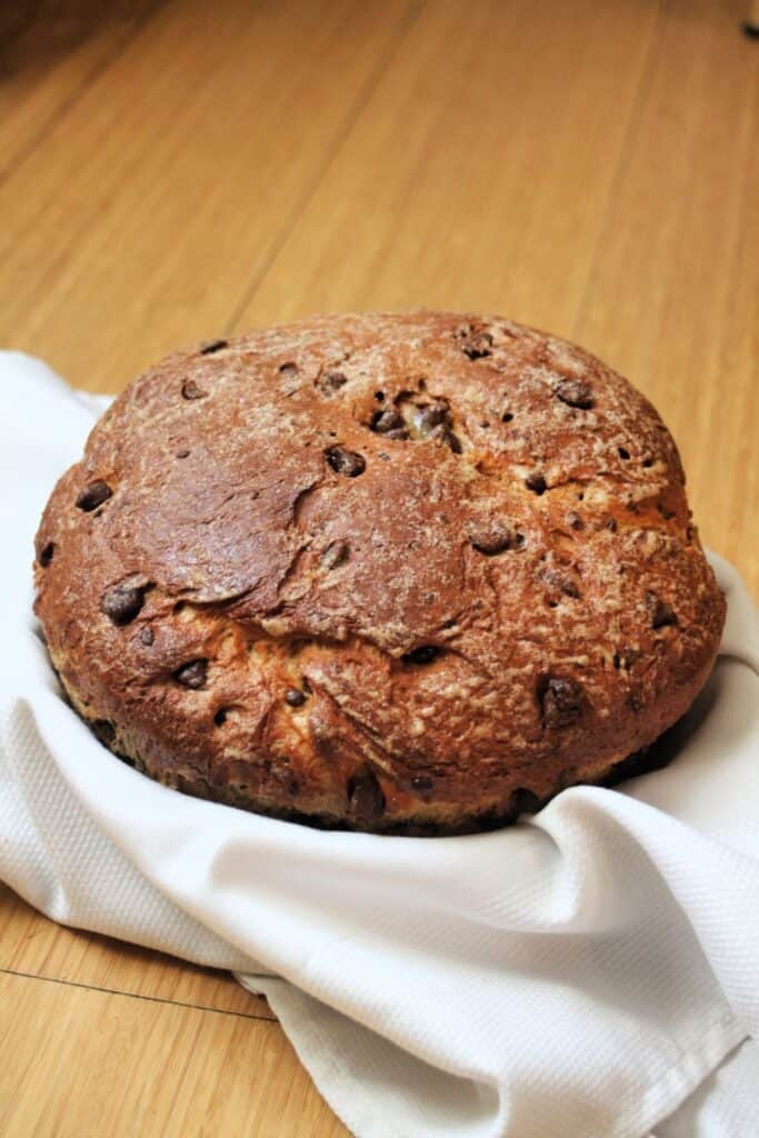 A round loaf of chocolate chip bread in a white linen lined basket.