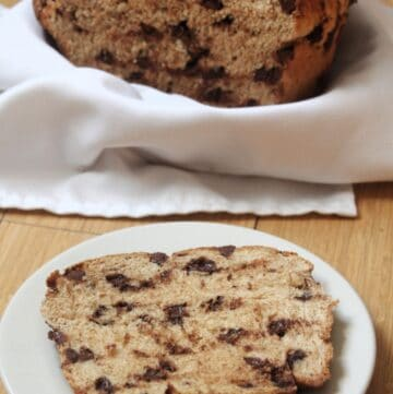 A slice of chocolate chip bread on a plate with remaining loaf sitting in a linen lined basket in the background.