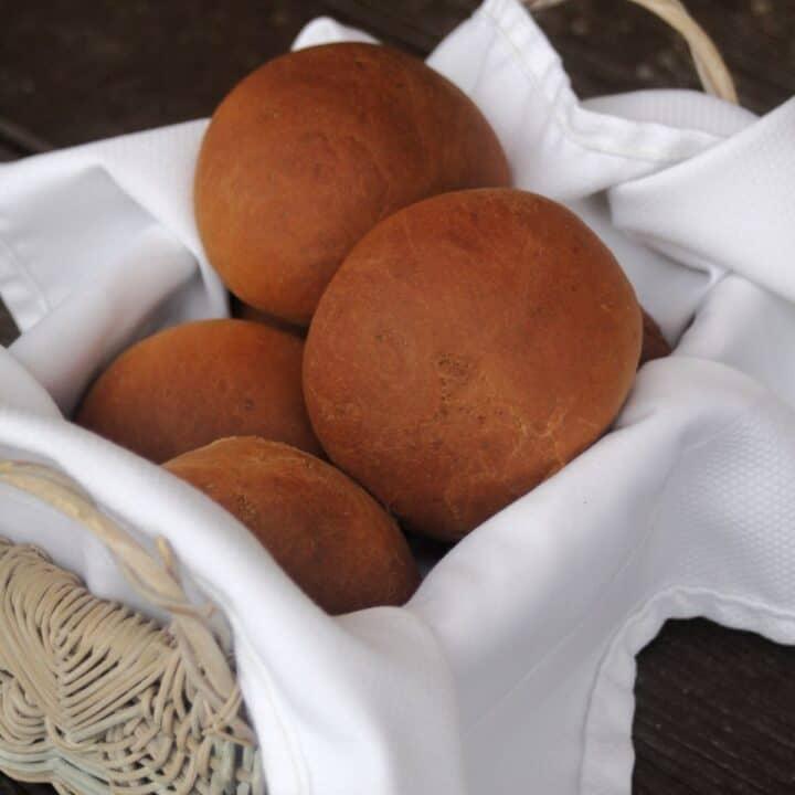 Dark molasses dinner rolls stacked in a white napkin lined basket.