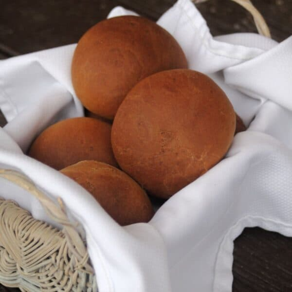 Molasses brown bread rolls stacked in a white napkin lined basket.
