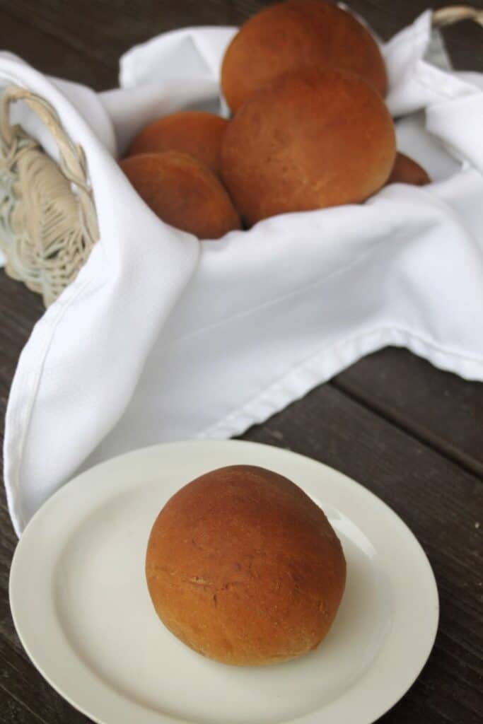 a molasses brown bread dinner roll on a white plate sitting in front of a napkin lined basket full of more rolls.