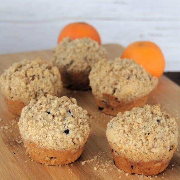 Dried cranberry muffins on a wooden board with fresh oranges in the background.