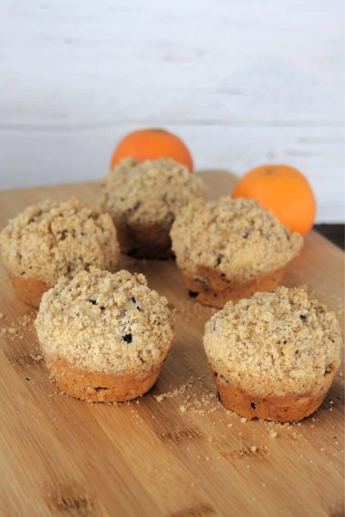 Dried cranberry muffins lined up on a wooden cutting board with oranges in the background.