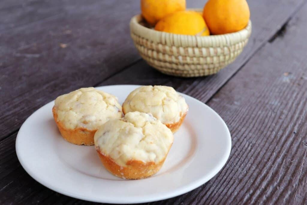 3 lemon muffins on a white plate with a basket fresh meyer lemons in the background.