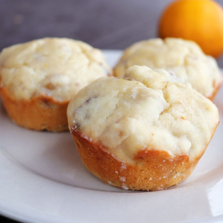 3 lemon muffins on a white plate with a fresh meyer lemon in the background.