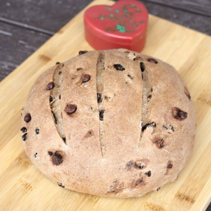 A round loaf of pumpernickel raisin bread on a cutting board with a red heart container in the background.