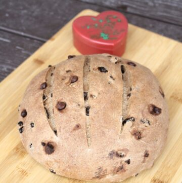 A round loaf of pumpernickel raisin bread on a wood cutting board with a red heart shaped container sitting behind it.