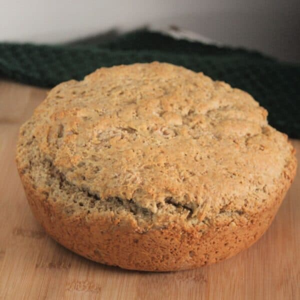 A round loaf of irish oatmeal soda bread sitting on wooden board with green cloth in background.