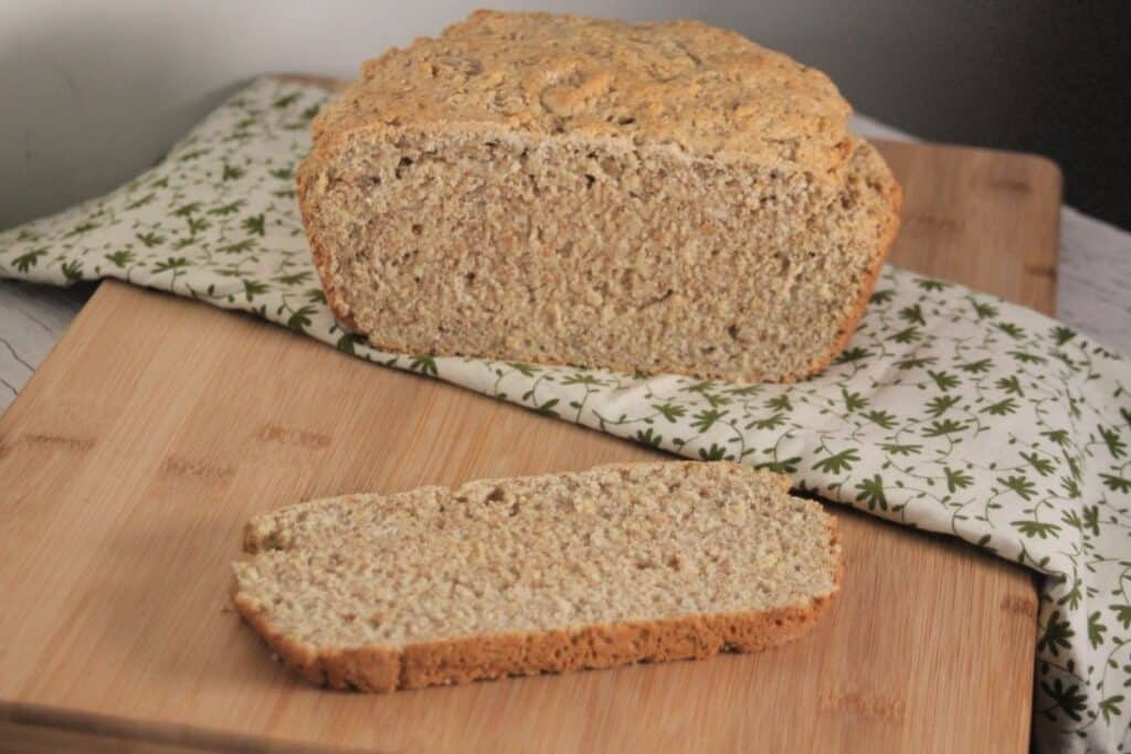 A slice of irish oatmeal soda bread sitting on a cutting board with remaining loaf sitting on a green and white linen in the background.