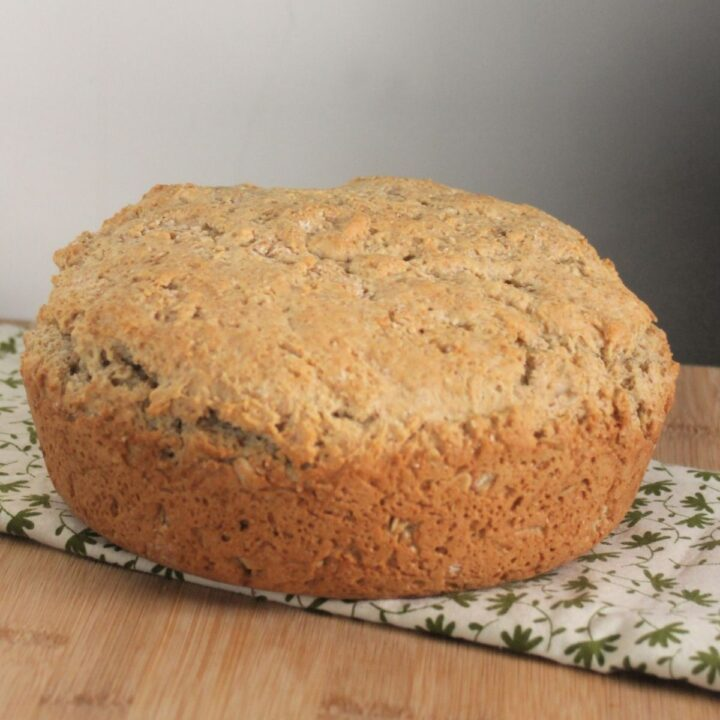 A round loaf of irish oatmeal soda bread sitting on a green and white table linen.
