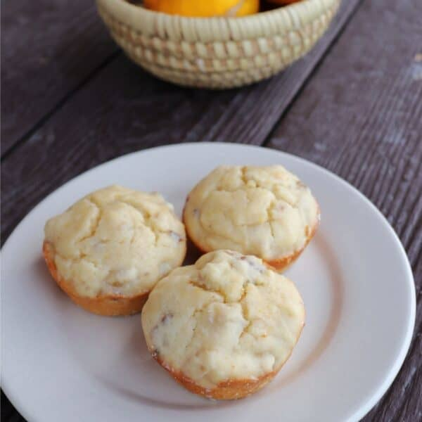 3 lemon nut muffins on a white plate with a basket of fresh meyer lemons behind it.