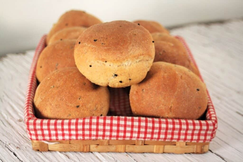 Pumpernickel rolls stacked inside a red & white checkered lined basket.