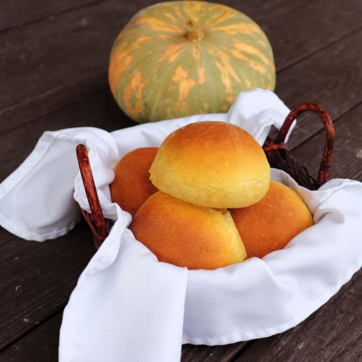 A white napkin lined basket full of pumpkin dinner rolls sitting in front of a green and orange striped pumpkin.