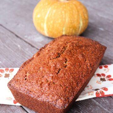 A loaf of pumpkin whole wheat nut bread sitting on a napkin with a pumpkin in the background.